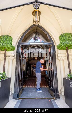 Ian, one of the management team, cleans front door handles at The Randolph Hotel, Oxford, ready to reopen after the Covid-19 lockdown on July 4th 2020 - Stock Photo