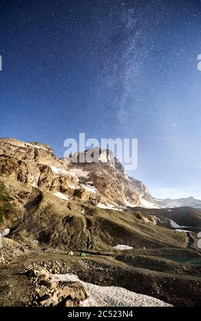 Fantastic view of majestic mountains and camp tents under blue sky with stars. Beautiful scenery of milky way over mountain peak and rocky hills. Concept of travelling in Alps, galaxy and nighttime. - Stock Photo