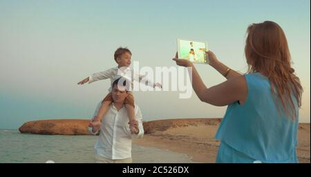 Little son riding on fathers neck and imitating plane while walking on the beach. Mother using touch pad to take family vacation photos - Stock Photo