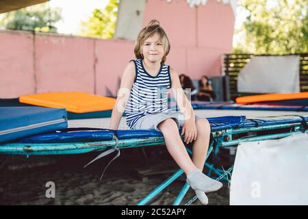 The theme of childhood, sports and health. Little boy gymnast resting in trampoline training session. A child athlete sits on a trampoline and looks - Stock Photo
