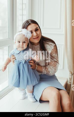 Smiling mother sitting by a window with her baby daughter - Stock Photo