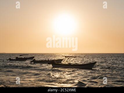 Boats in the water at Playa Blanca beach at Sunset, Cartagena, Colombia - Stock Photo