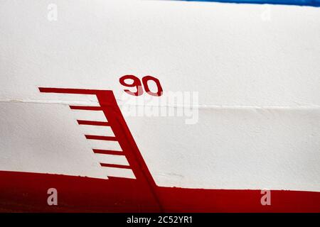 Marking the water depth on the hull of a vessel with the number '90', red and white - Stock Photo