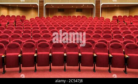 Panoramic view of an empty cinema hall. Rows of red theater seats. Panorama of the modern movie theater interior. Comfort chairs in conference room fo