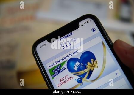 Viersen, Germany - June 30. 2020: Close up of mobile phone screen hold by male hand with Payback  app showing shopping points (focus on 511) - Stock Photo