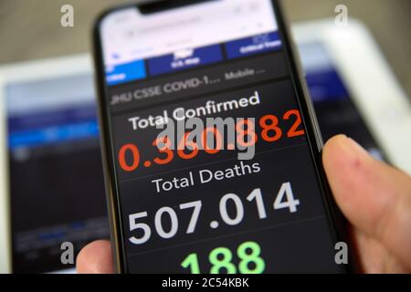 Viersen, Germany - June 30. 2020: Close up of mobile phone screen hold by male hand with counter of John Hopkins university showing numbers of worldwi - Stock Photo