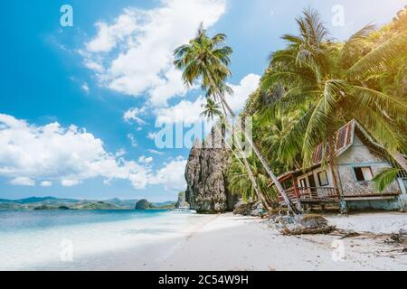 Vacation holiday on Palawan - El Nido island hopping tour. Lonely deserted hut under palm trees, cliff rocks in background.
