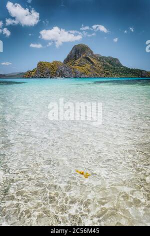 El Nido shallow bay with crystal clear water and Cadlao island on sunny day, Palawan, Philippines. - Stock Photo