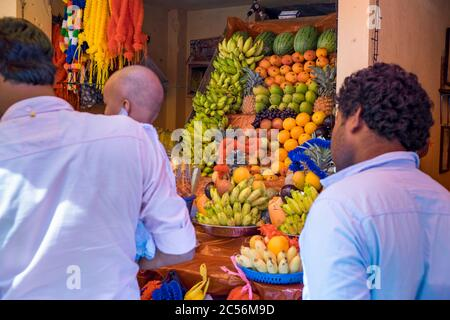Men stand in line in front of a small fruit stall in Sri Lanka's market - Stock Photo