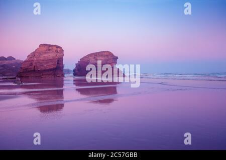 Rocky sea coast at sunrise. Beach Playa de Las Catedrales in Ribadeo, Spain, Europe - Stock Photo
