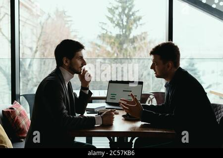 Two businessmen talking about new opportunities sitting with laptop at desk, planning project, considering business offer, sharing ideas
