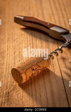 Corkscrew on sunlit wooden table with cork - Stock Photo