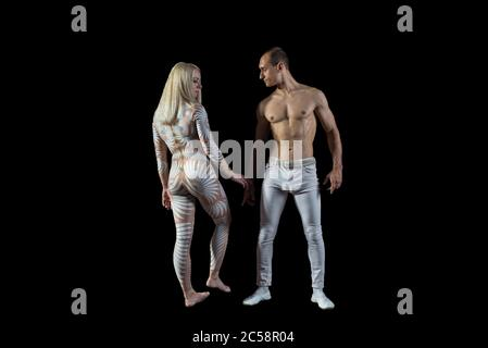 Man and woman with acrobatics pose portrait of acrobats guy with a girl in white isolated on a black background. Acrobatic abilities, sport dancing, a - Stock Photo