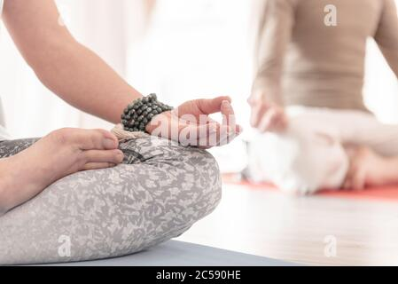 Close-up of feminine and masculine arms and crossed legs during meditation. How to Keep Your Arms in the Air for a Kriya or Meditation.