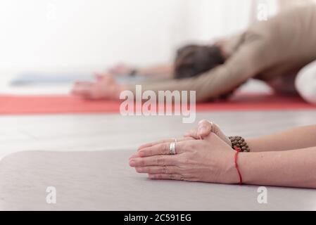 Close-up of feminine and masculine arms during meditation.  Shashankasana position. Rabbit Pose. Seguence of Surya namaskar. Greeting to the Sun. How