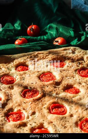 Focaccia homemade italian bread baked with sliced cherry tomatoes, sea salt and rosemary herbs