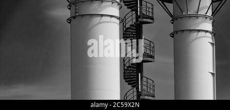 Section of a metal spiral staircase on an industrial building with two chimneys in black and white, copy space - Stock Photo