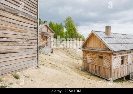 Wooden houses in small village near Volga river in cloudy day - Stock Photo