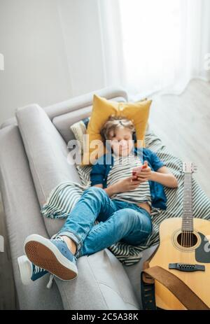 Preteen boy lying with guitar on cozy sofa dressed casual jeans and new sneakers listening to music and chatting using wireless headphones connected w