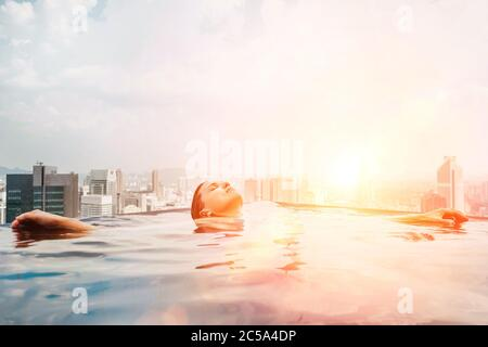 Young female relaxing in top roof infinity swimming pool with city view to the modern business center downtown with a skyscrapers and towers. Luxury v - Stock Photo