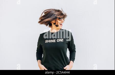 Free feeling happy smiling woman posing in black sweatshirt with positive print Shine On. She rotating a head bacause a cheerful mood. - Stock Photo
