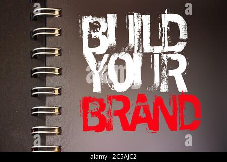 Build Your Brand words on a page of spiral copybook white and red on black. Branding rebranding marketing business concept