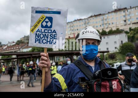 An Alcoa worker holding a placard during the demonstration.Thousands of people marched to Santiago de Compostela at the regional government following Alcoa works council demonstrations that started a month ago against the collective dismissal of up to 534 workers from its two factories in San Cibrao. The demonstration is marked by the proximity of the elections on July 12th of the regional government of Galicia. - Stock Photo