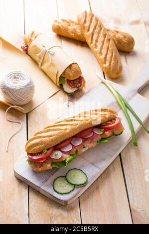 Fresh submarine sandwiches with varieties of fillings on wooden background - Stock Photo