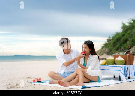 Asian young couple sitting on the picnic blanket and eating watermelon in the beach and near sea with tropical fruit in background. Summer, holidays, - Stock Photo