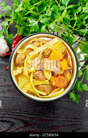 Central Asian national dish Lagman of meat, noodles and vegetables in bowl on a napkin, garlic, parsley on wooden board background from above - Stock Photo