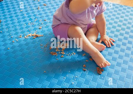 baby's bare feet on the mat with crushed biscuits around - Stock Photo