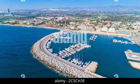 Aerial bird's eye view of Zygi fishing village port, Larnaca, Cyprus. The fish boats moored in the harbour with docked yachts and skyline of the town - Stock Photo