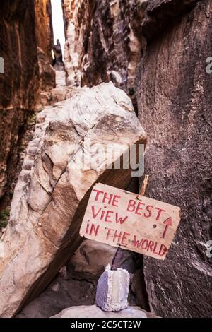 A humorous tourist sign in the canyon of Siq Al-Barid or Little Petra in Jordan. - Stock Photo