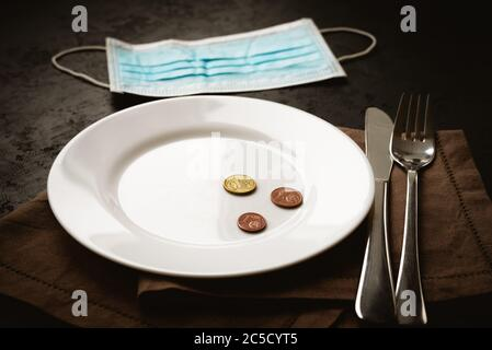 Euro cents coins on white empty plate and medical mask on black background. Lack of money during quarantine, poverty and unemployment concept - Stock Photo