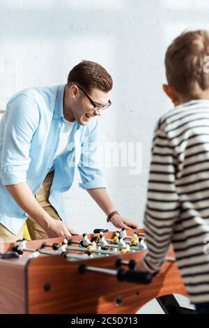 selective focus of cheerful man playing table football with son - Stock Photo