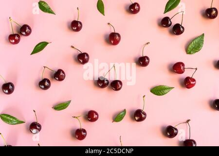 Cherry pattern. Flat lay of cherries on a pink background. Top view.