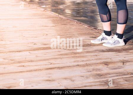 unrecognizable female runner legs ready with running shoes on a wooden floor, sport concept and healthy lifestyle, copy space for text - Stock Photo