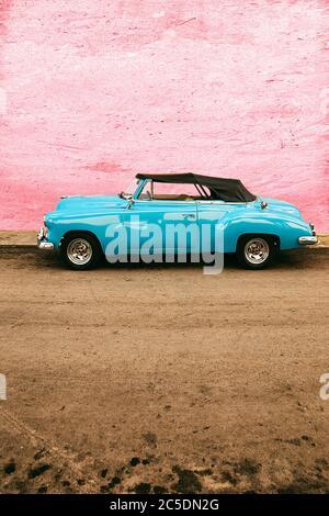 old blue car parked on pink wall, havana - cuba