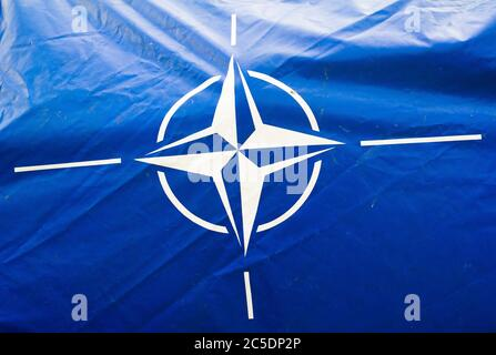 Ostrava, Czechia - September 18, 2016: Dirty and wrinkled blue canvas with flag of NATO ( North Atlantic Treaty Organization ). Military alliance - Stock Photo