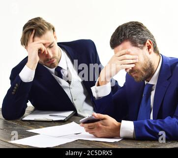 Overworked office workers. Men with tired, worried faces read about fail. Employees in formal suits look stressed and depressed. Workaholic, paperwork, deadline concept. Overtime and frustration. - Stock Photo