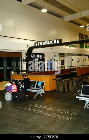 2nd July 2020, Luton Airport, UK: A passenger wearing a face mask sits next to a closed Starbucks cafe in the departure lounges of Luton Airport. Numbers of flights from the UK to some European countries are starting to increase, and governments are expected to announce air bridges between countries soon to facilitate travel and tourism. The economic impact of the virus on retail and other sectors will be severe, with many businesses still shut