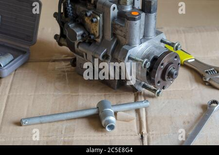 High pressure fuel pump on a work bench next to wrenches. Detection of diesel fuel automotive equipment. Car service, auto repair. - Stock Photo