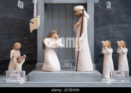 Wooden figurines depict a Christmas nativity scene in a simple wooden stable. - Stock Photo