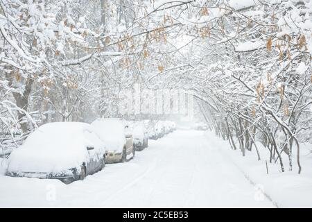 Street during snowstorm at winter in Moscow, Russia. Cars covered with snow. Scenic view of a snowy city street. Moscow snowfall background. Cold sile - Stock Photo
