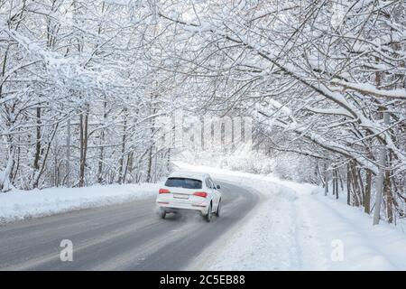Road in winter forest. White car goes across woods after snowfall. Scenic view of tunnel with snowy trees. Nice scenery of frozen way covered snow. - Stock Photo