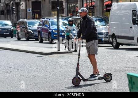 London, UK.  2 July 2020. A man rides a personal electric scooter (e-scooter) in Regent Street.  The Department of Transport will allow rental e-scooters to become legal on roads in Great Britain from 4 July, for a 12 month trial period, to try to ease pressure on public transport during the coronavirus pandemic.  Riders need a full or provisional car, motorcycle or moped licence to use the vehicles, and they must be aged 16 or over.   Currently, it is an offence to ride personal e-scooters on a UK public road, cycle lane or pavement. Credit: Stephen Chung / Alamy Live News - Stock Photo