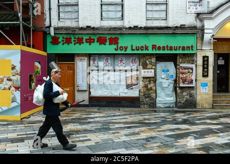 London, UK.  2 July 2020. A man wearing face protection on his head walks by a closed restaurant in Chinatown.  Restaurants and other businesses have struggled during the coronavirus pandemic lockdown.   Credit: Stephen Chung / Alamy Live News - Stock Photo