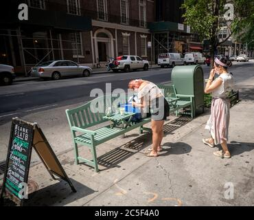 Woman photographs her drink outside a restaurant in the NoMad neighborhood in New York on Tuesday, June 30, 2020 as Phase Two of the city's reopening plan takes effect. Al fresco dining is now allowed with restrictions as well as in store shopping. (© Richard B. Levine) - Stock Photo