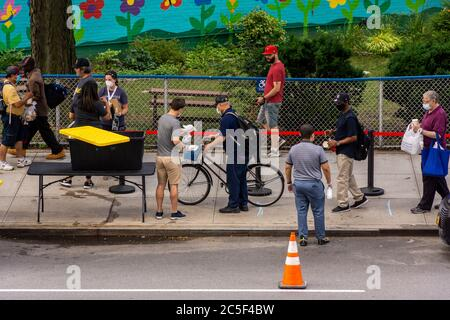 People in need line up for clothing and food at the Relief Bus social services in the Chelsea neighborhood of New York on Wednesday, July 1, 2020. (© Richard B. Levine) - Stock Photo