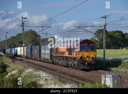 DB Cargo class 66 diesel locomotive 66137 on the electrified west coast mainline with a intermodal container freight train - Stock Photo